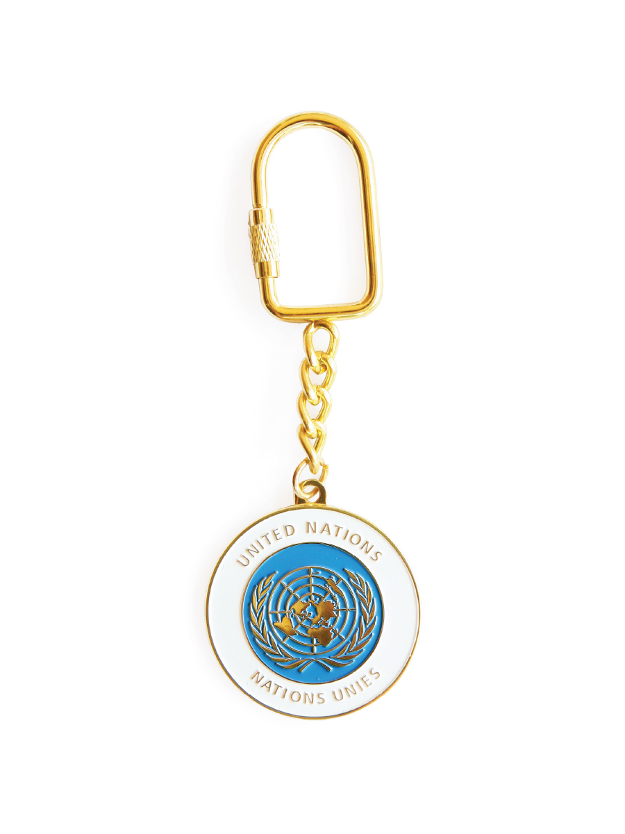 An image of a circular, white enamel keychain with painted blue circle and the UN Emblem etched into the gold plated surface.