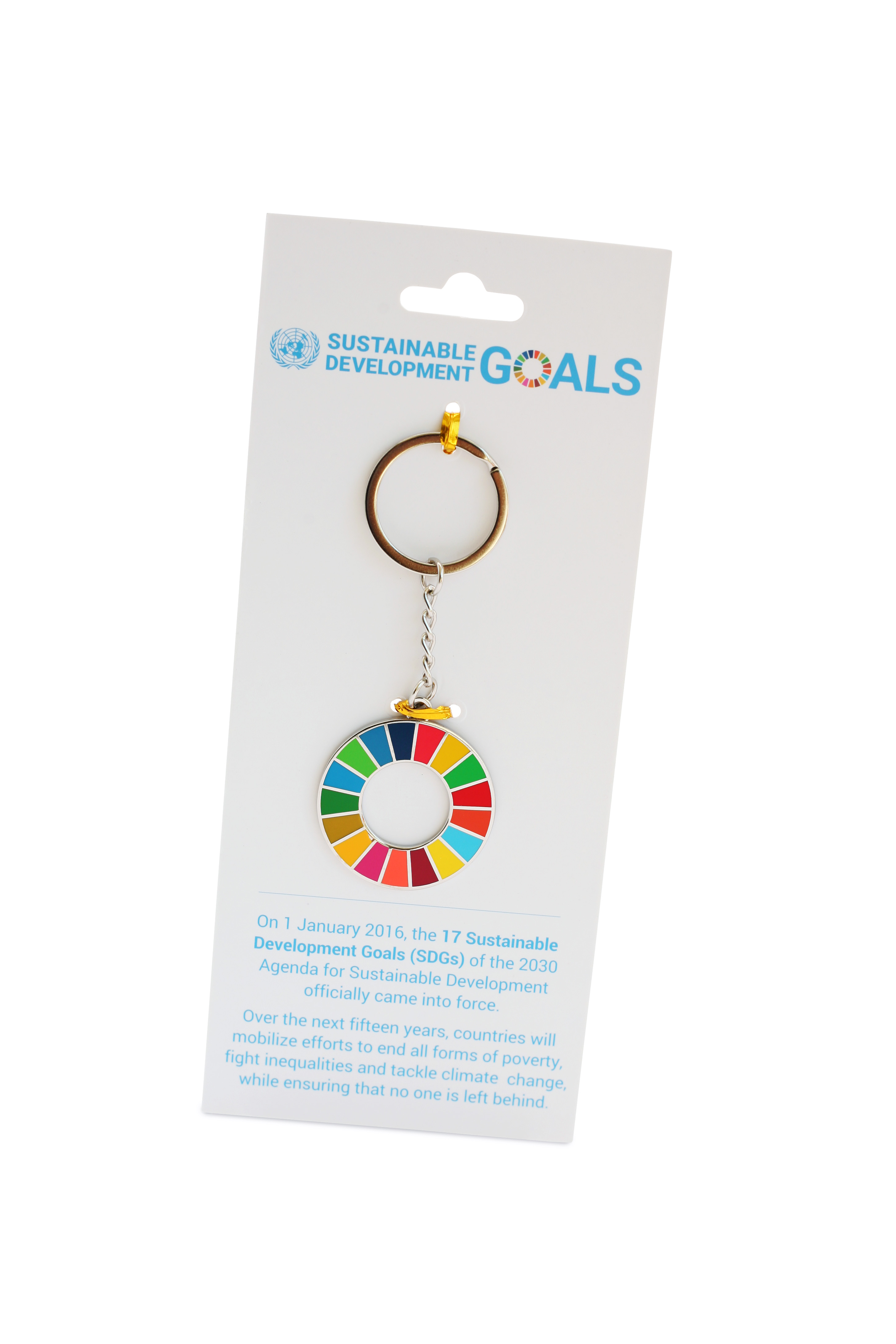 A picture of a keychain in the shape of the Sustainable Development Goals wheel on a cardboard backer.