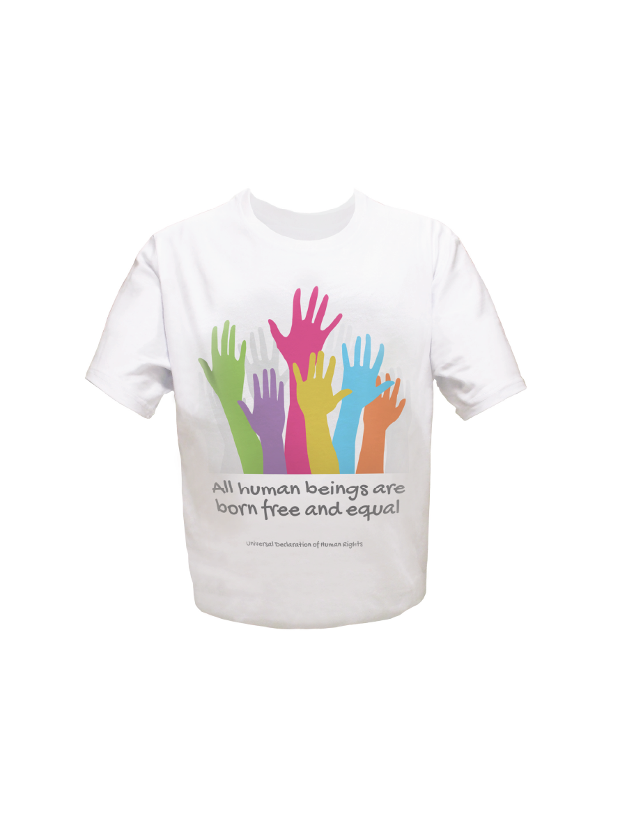 An image of a white youth organic cotton t-shirt with text of Article 1 of the Universal Declaration of Human Rights printed on the front of the shirt and emblazoned with artwork depicting hands in various colours.